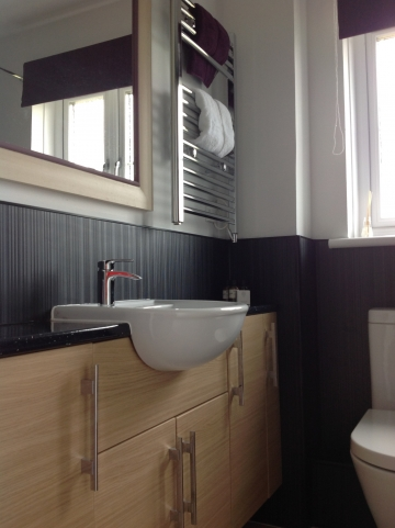 Bathroom with bath, toilet, electric shower and vanity unit with sink, heated towel rail.